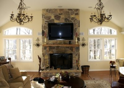 Custom TV installation over stone fireplace